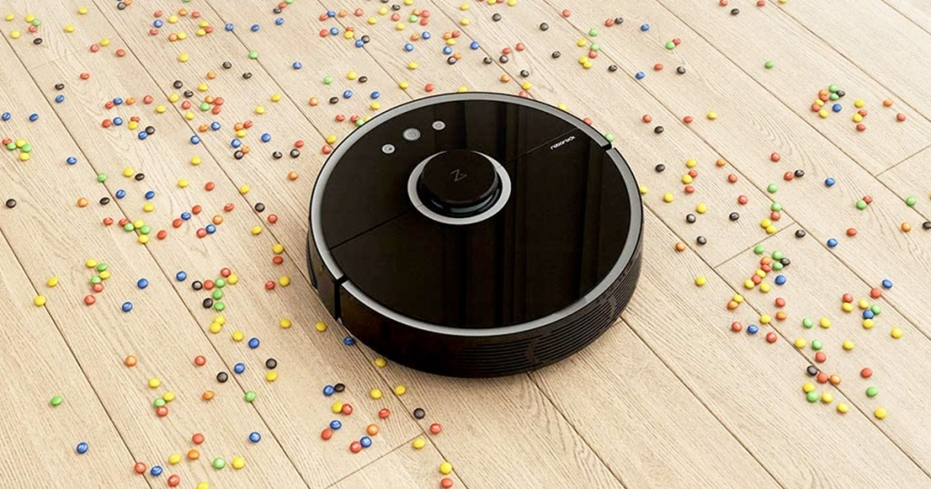 round black robotic vacuum cleaning up spilled candy on hardwood floor
