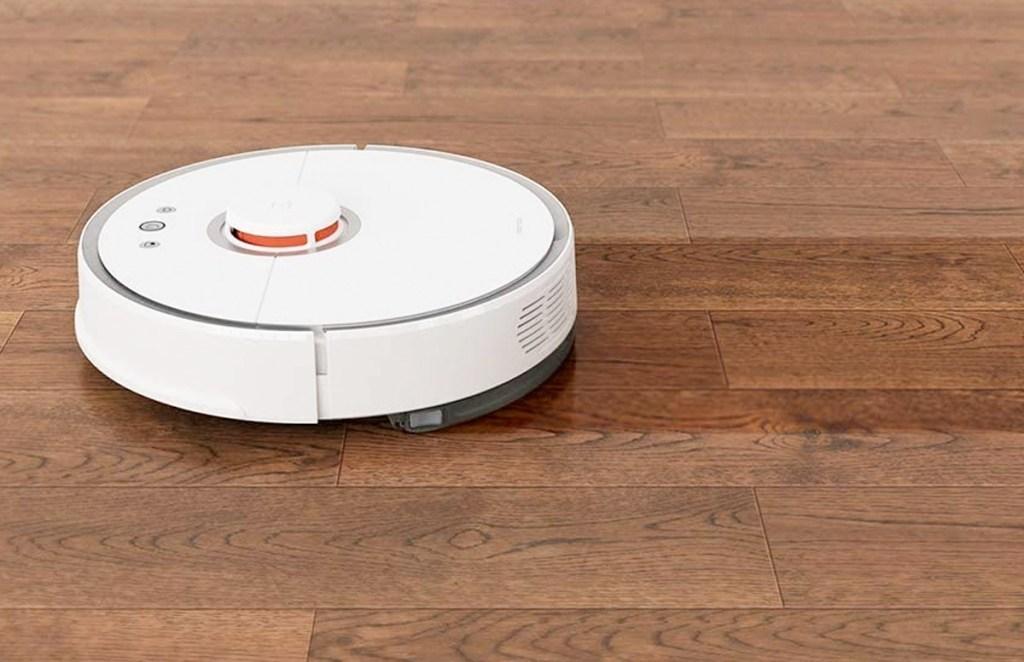 white round robotic vacuum mopping on hardwood floor