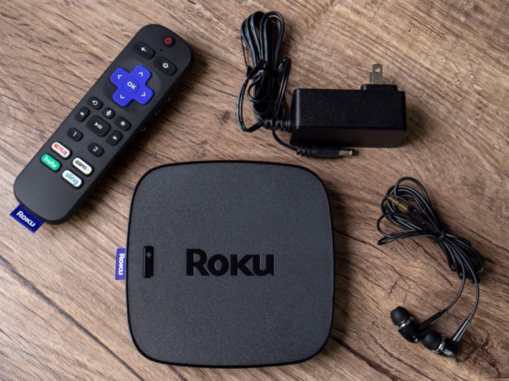 streaming media player, remote, charger, and headphones on table
