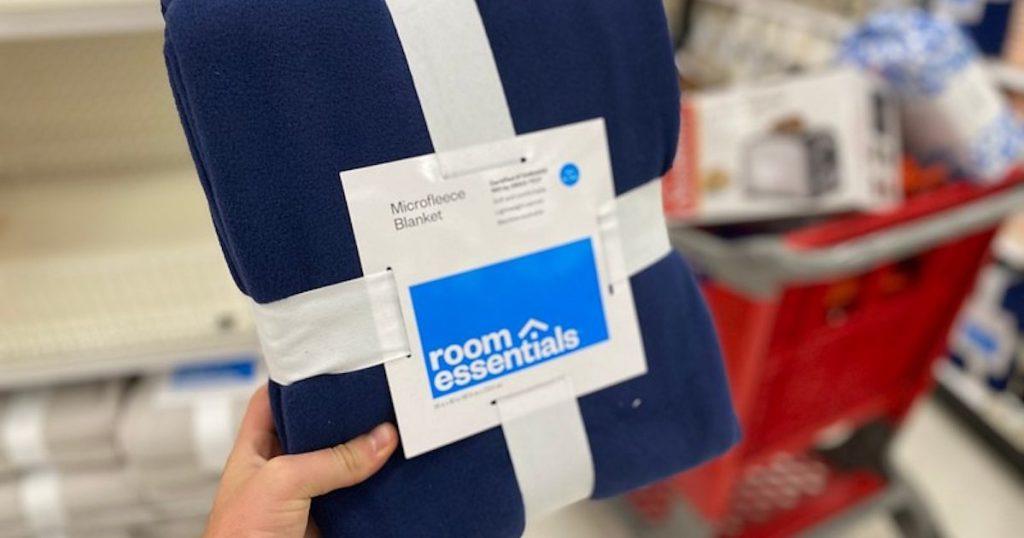 man hand holding dark blue Room Essentials Twin/Twin XL Fleece Blanket