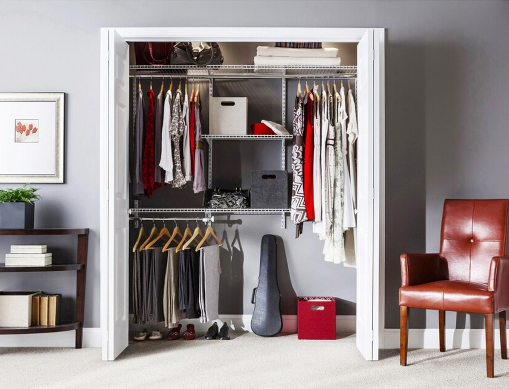 closet with an organizer system with metal shelves and racks to organize clothing and shoes