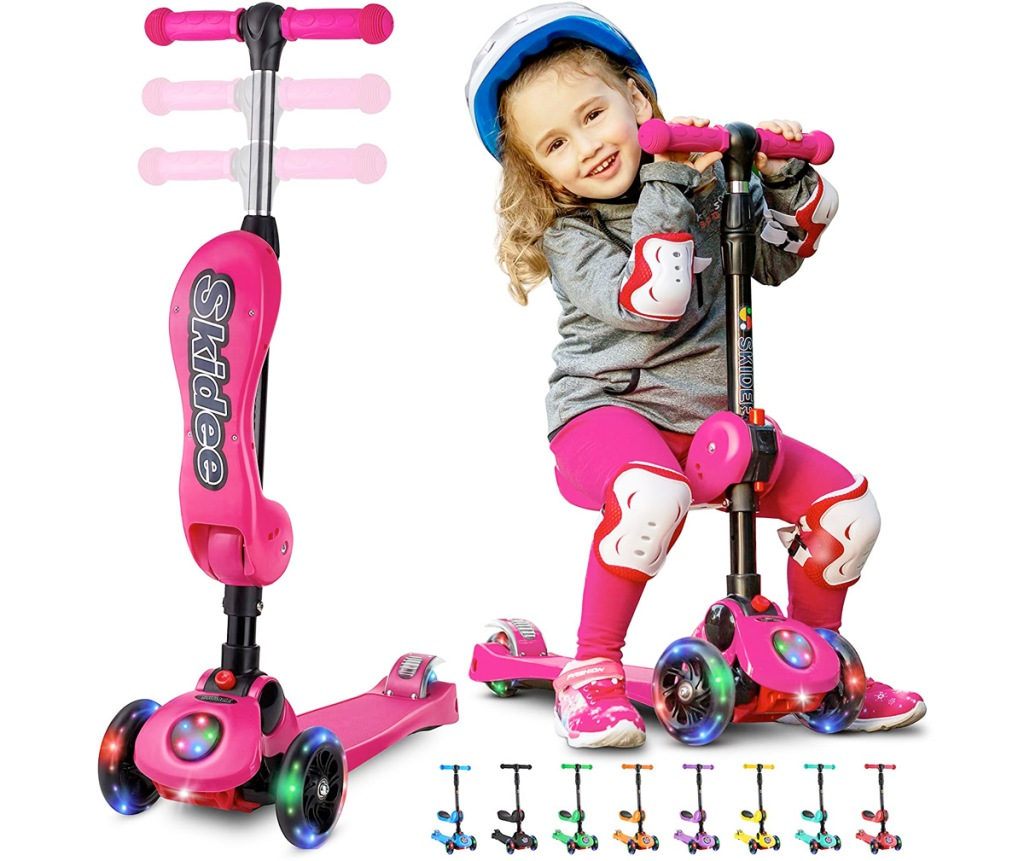 pink adjustable scooter with seat and led wheels with girl sitting on scooter seat wearing helmet