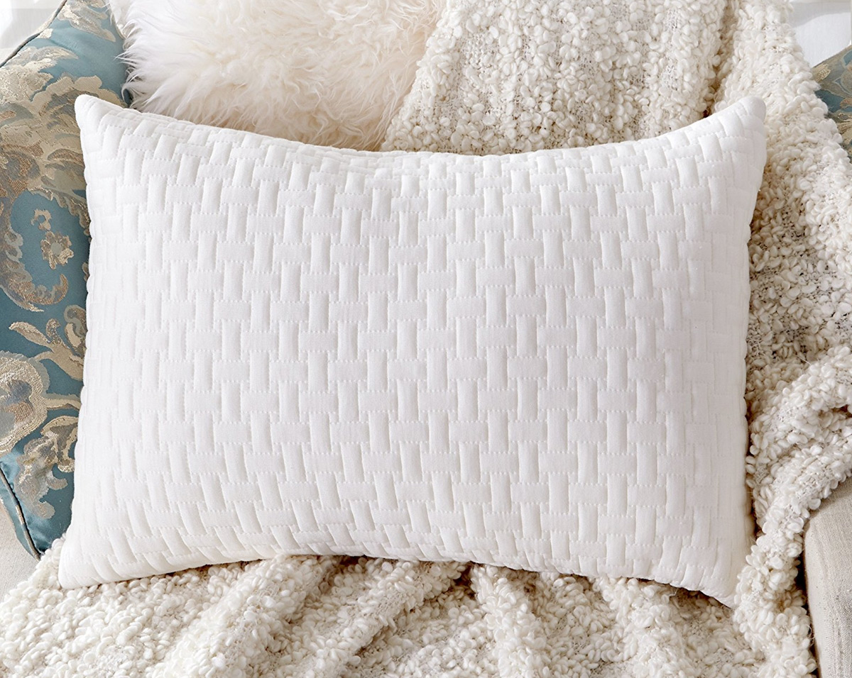 white memory foam bed pillow on a white fuzzy blanket on a chair