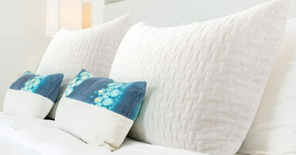 two white memory foam pillows and two blue throw pillows on a bed