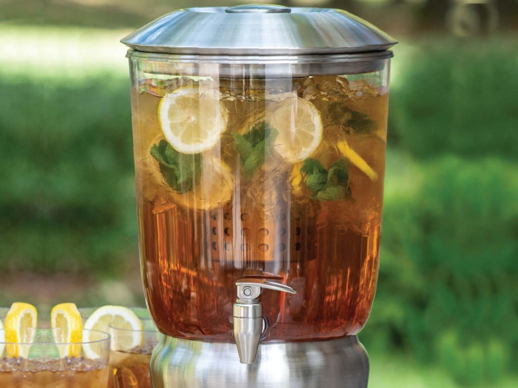 large chrome beverage infuser sitting next to glasses of iced tea and lemons