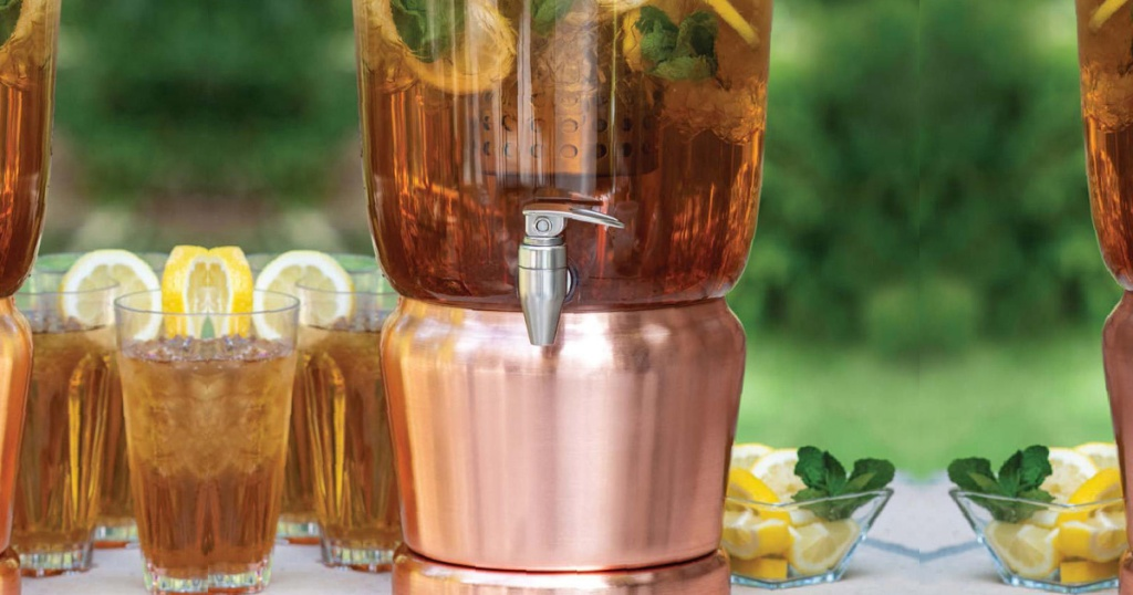 large copper beverage infuser sitting next to glasses of iced tea and lemons