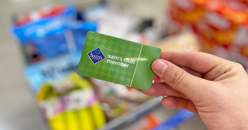 person holding up a green Sam's Club membership card in front of full shopping basket