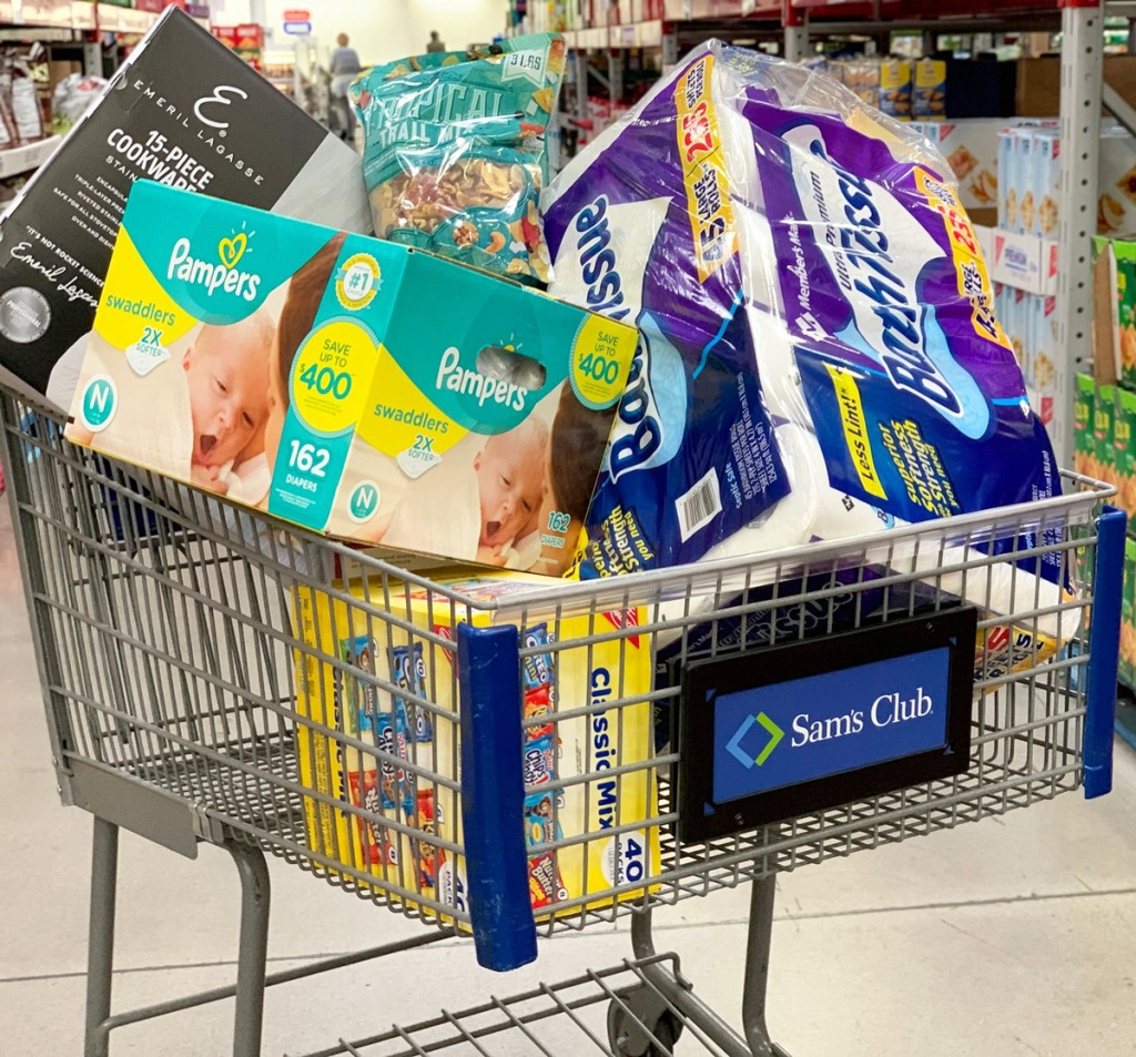 Sam's Club shopping cart filled with bath tissue, pampers diapers, trail mix, and more