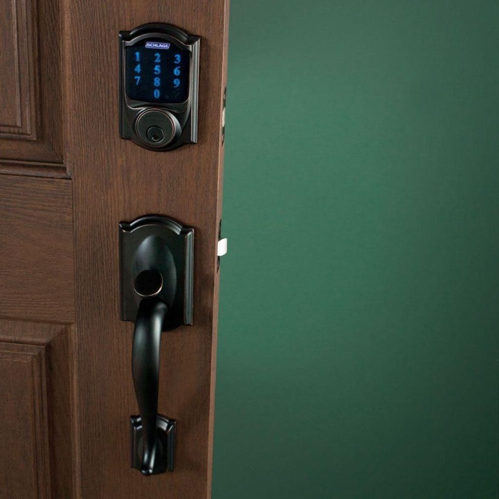 black schlage smart lock on brown door with green painted wall