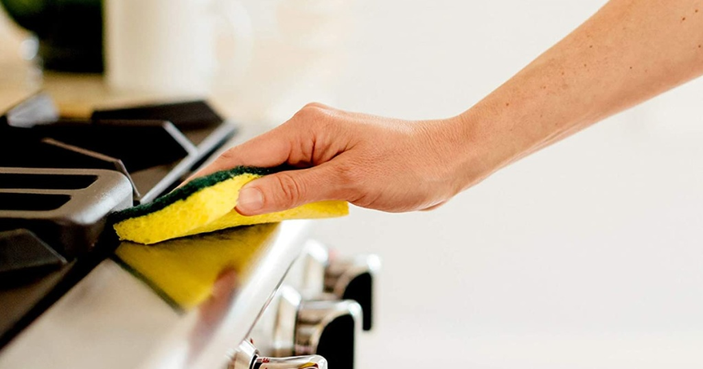 hand holding a scotch brite heavy duty sponge wiping down a kitchen stove