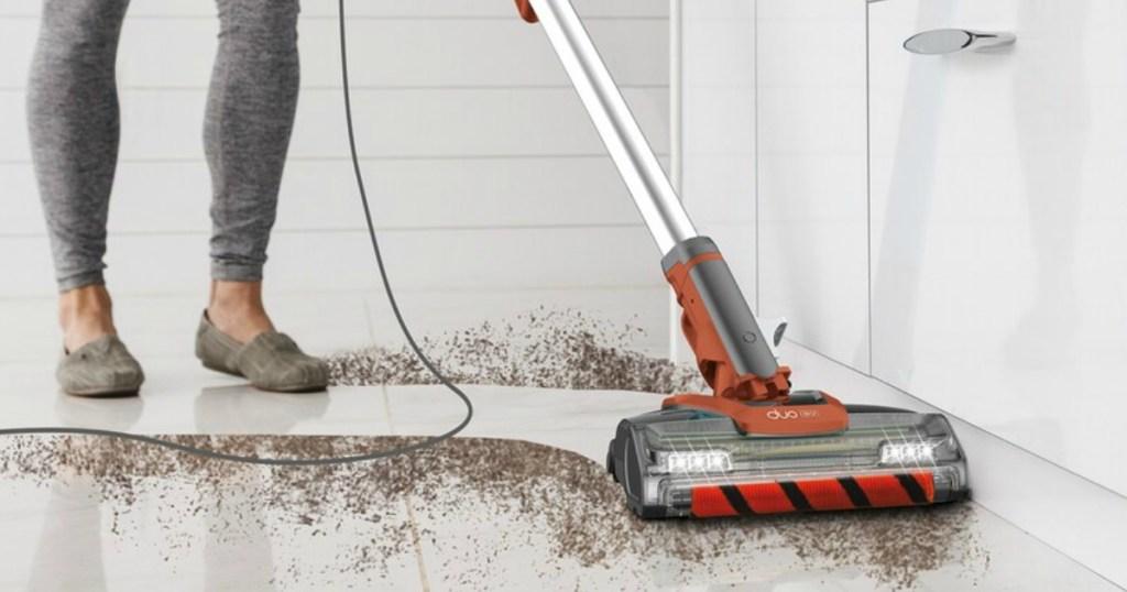 person vacuuming up dirt