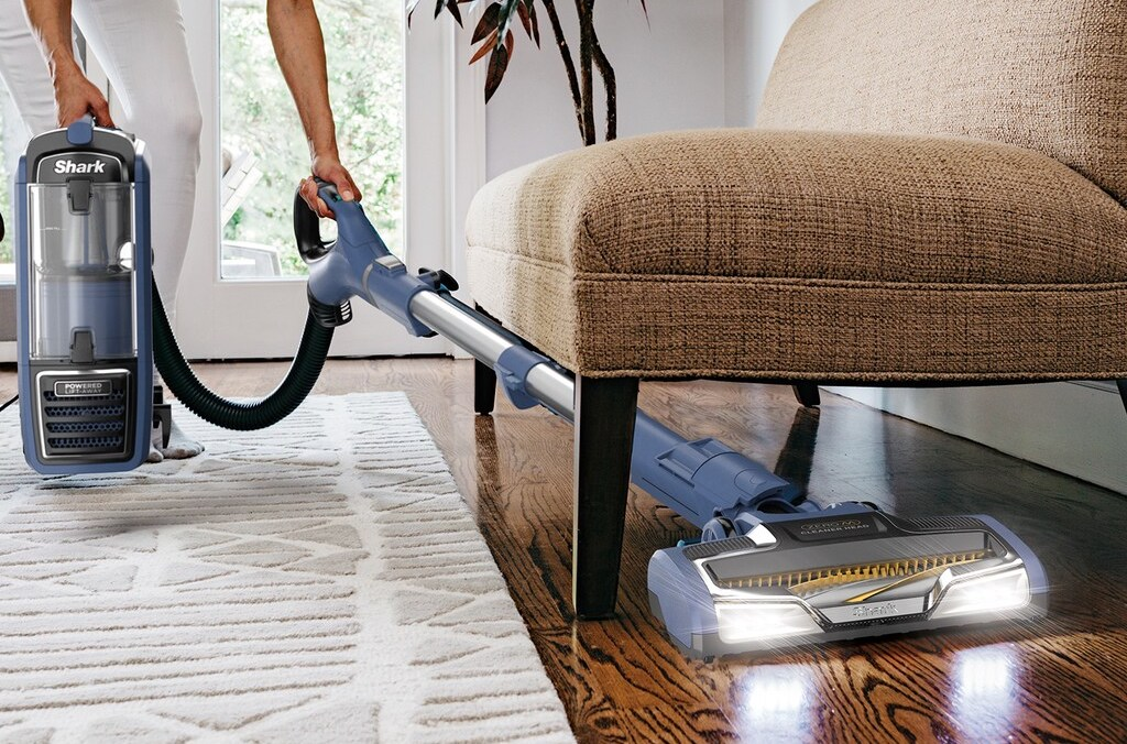 person vacuuming under furniture