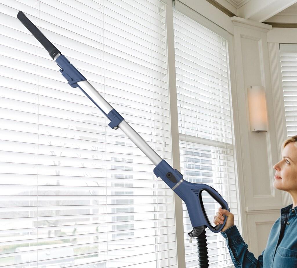 woman vacuuming blinds