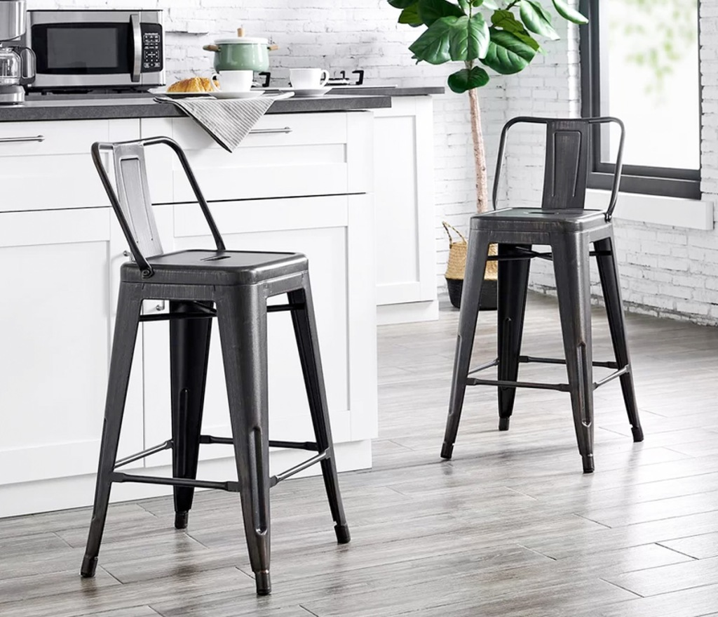 two black metal industrial style barstools with backs at white counter in kitchen