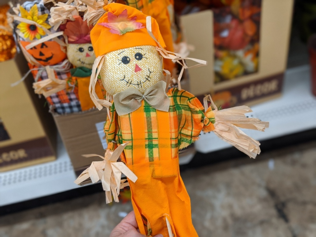hand holding orange colored standing scarecrow at dollar tree