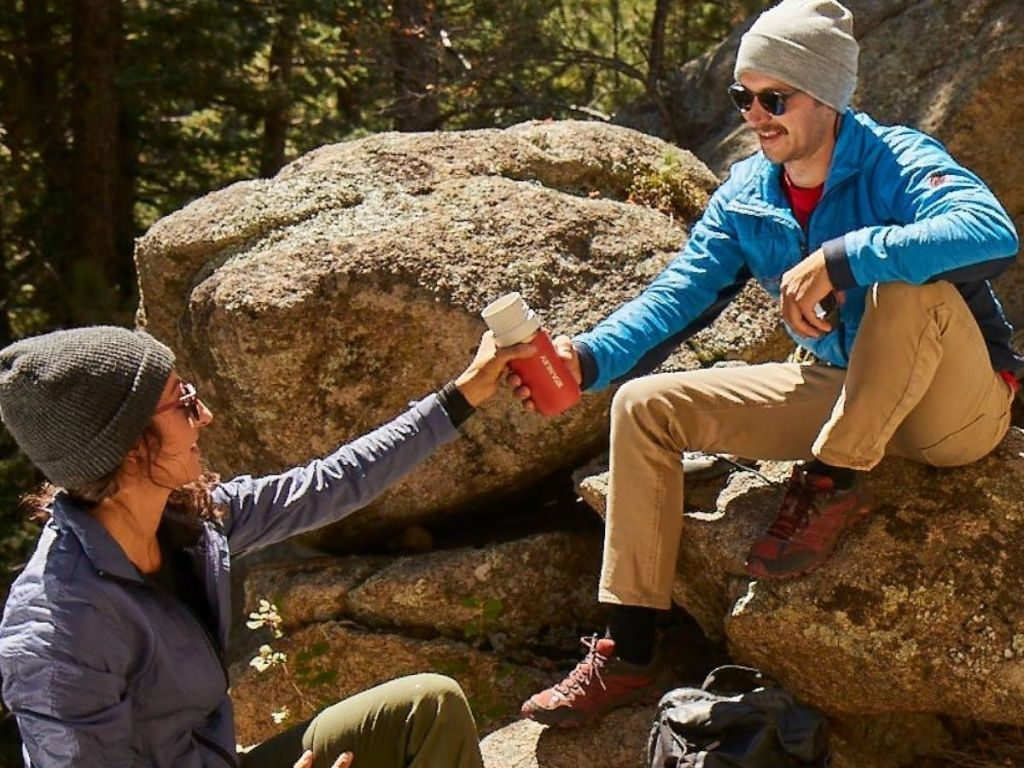 couple sharing reusable water bottle while sitting on rocks out in nature