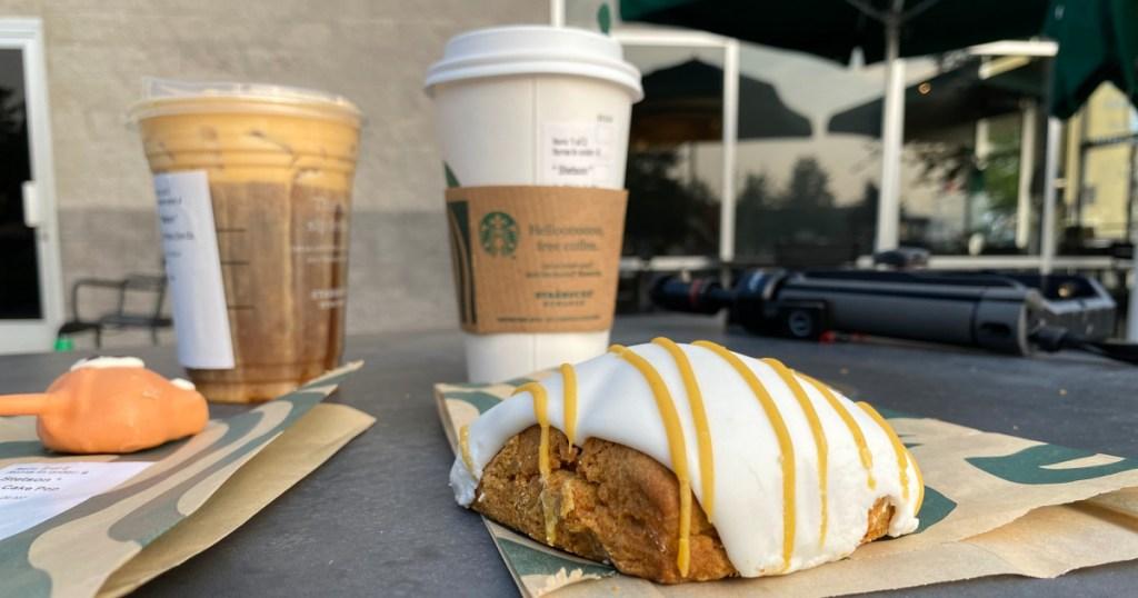starbucks pumpkin scone on table next to fox cake pop, pumpkin spice latte, and pumpkin cream cold brew