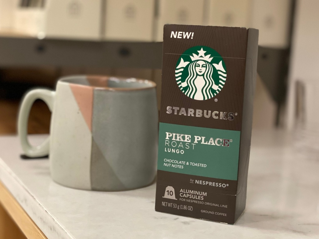 A box of Starbucks Pike Place Nespresso Pods sitting next to a mug on a counter