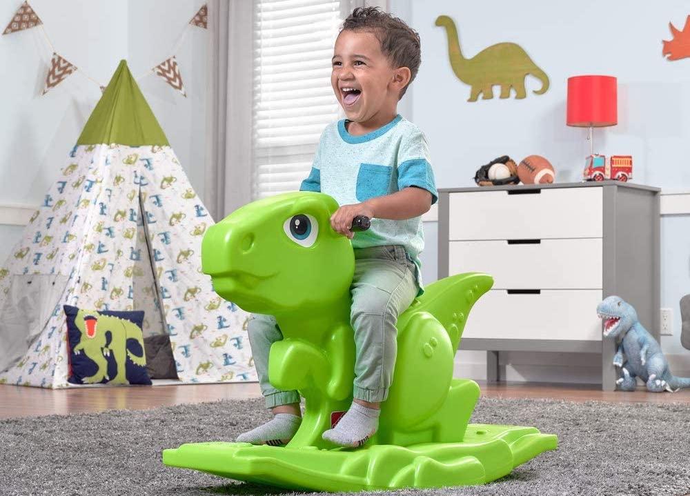 boy on a dinosaur rocker toy