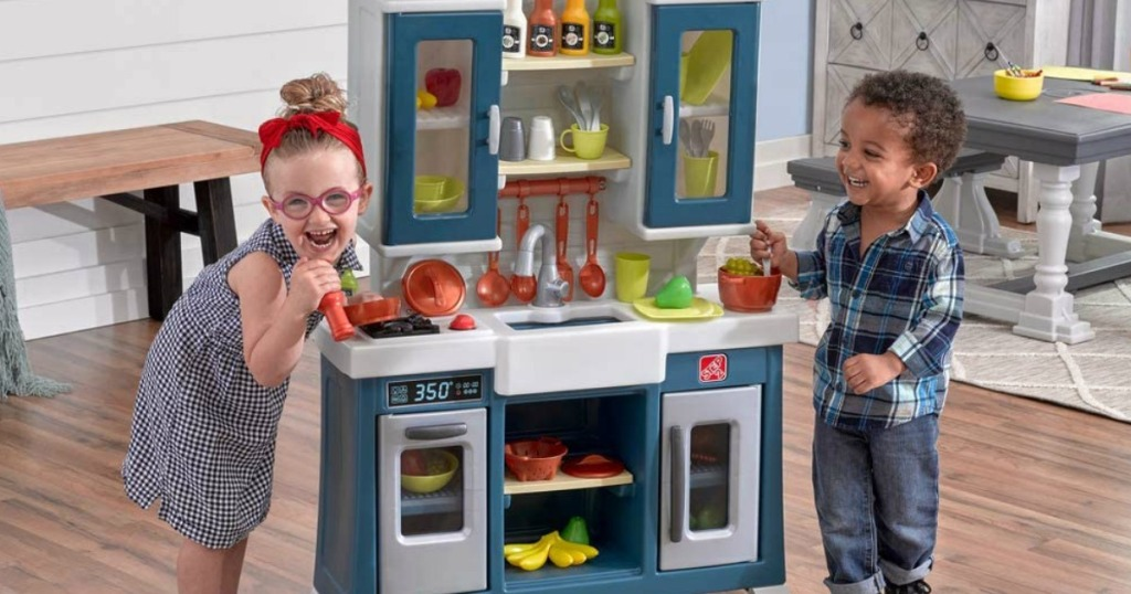 kids playing with a toy kitchen
