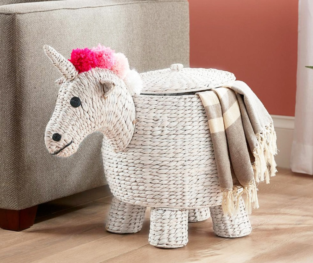 white unicorn sotrage basket with pink hair and blanket coming out from lid