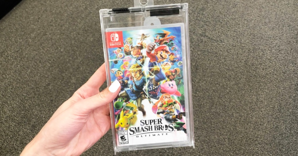 person with white finger nails holding up the case for the Super Smash Bros Ultimate Nintendo Switch game