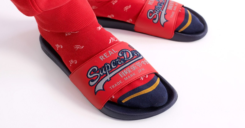 man wearing a pair of red slides with Superdry logo across the top with red sweatpants and red socks