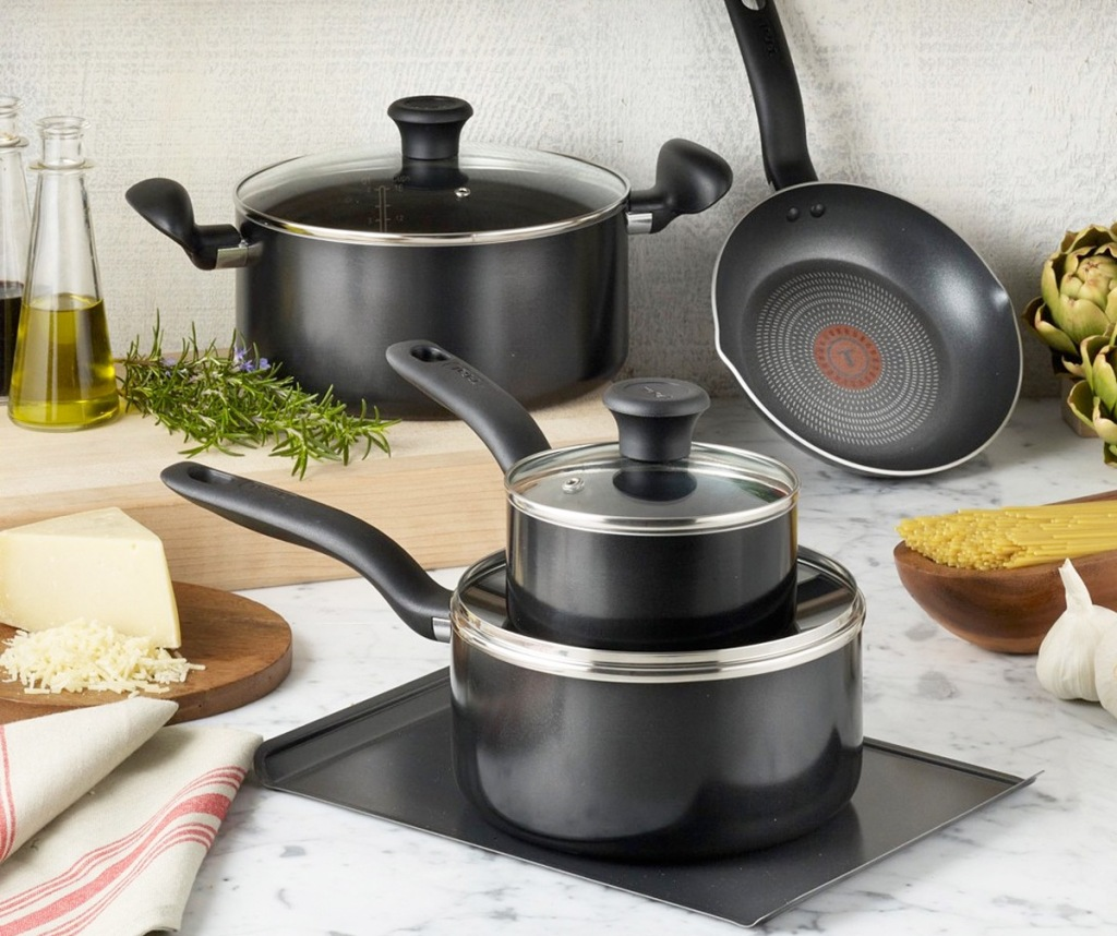black t-fal cookware set on kitchen countertop near foods and cutting board