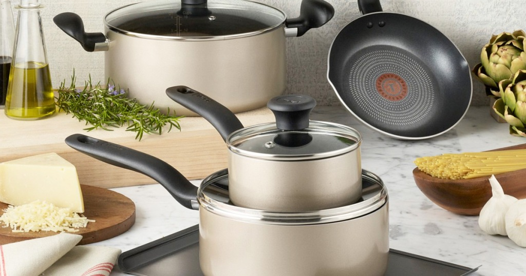 gold t-fal cookware set on kitchen countertop near foods and cutting board