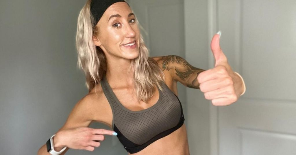 woman wearinga sport's bra and giving it a thumbs up