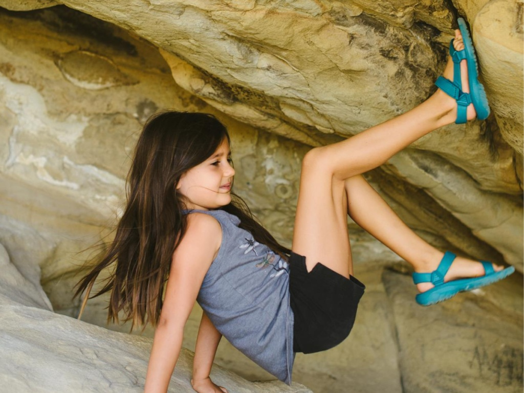 girl climbing rocks in cave