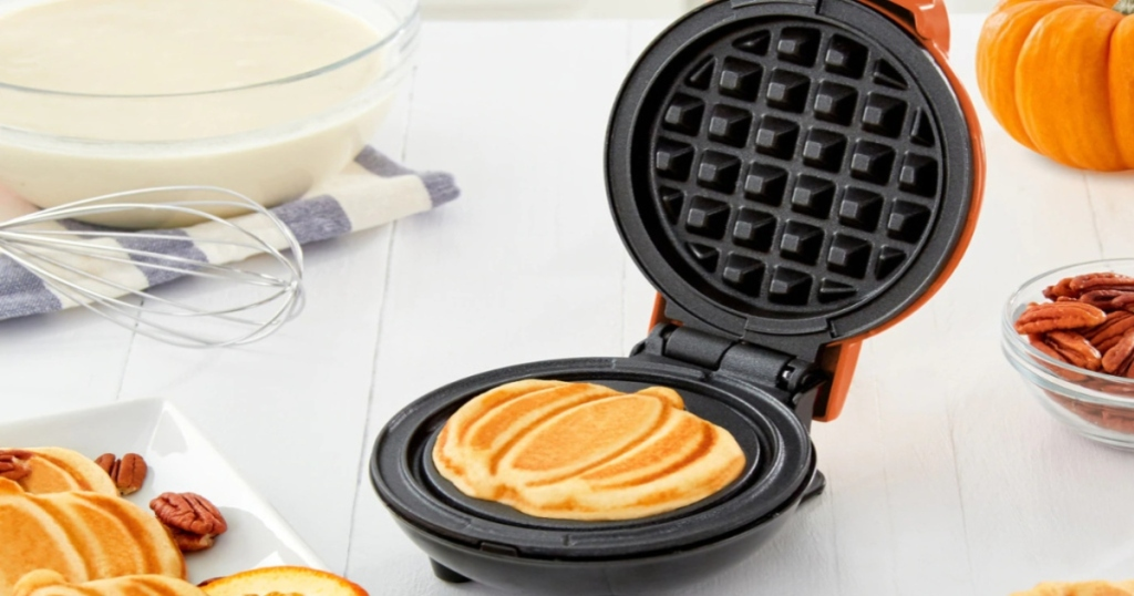 Dash Pumpkin shape waffle maker on a table with a bowl of batter and a plate of pumpkin waffles