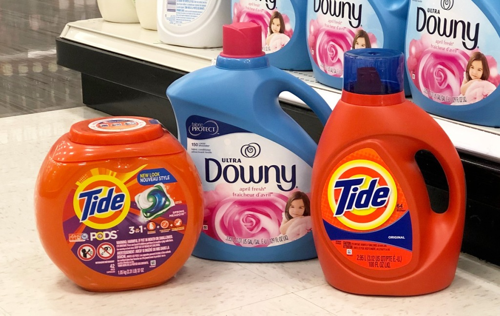 orange container of tide pods and tide liquid with a blue bottle of downy fabric softener grouped together