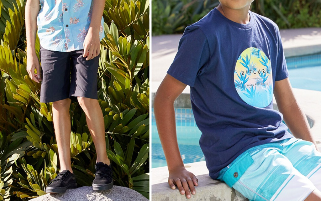 boy standing on rock wearing black shorts and blue tee and boy sitting by pool wearing blue billabong graphic tee and blue swim trunks