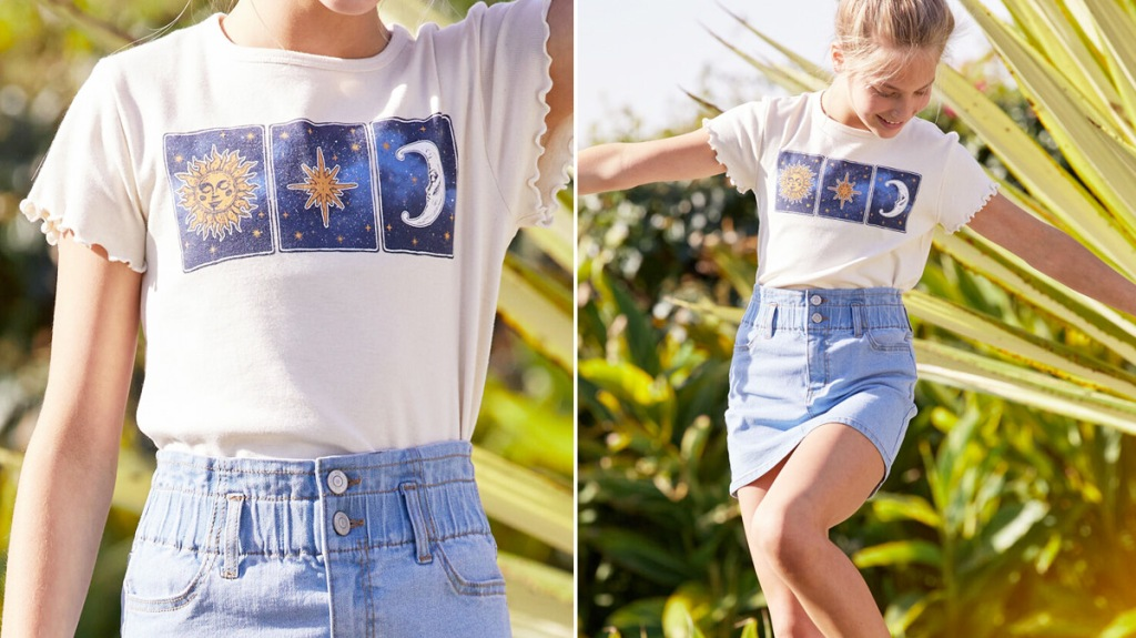 girl modeling a star and moon graphic tee with light wash denim skirt