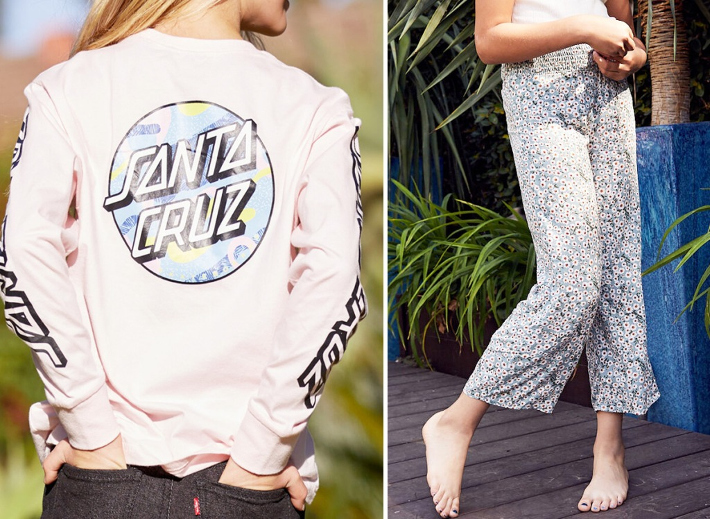 girl standing with hands in her back pockets wearing black jeans with light pink Santa Cruz long sleeve graphic tee and girl standing outside wearing white tee and floral print pants