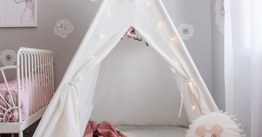 white kids teepee tent decorated with lights in bedroom