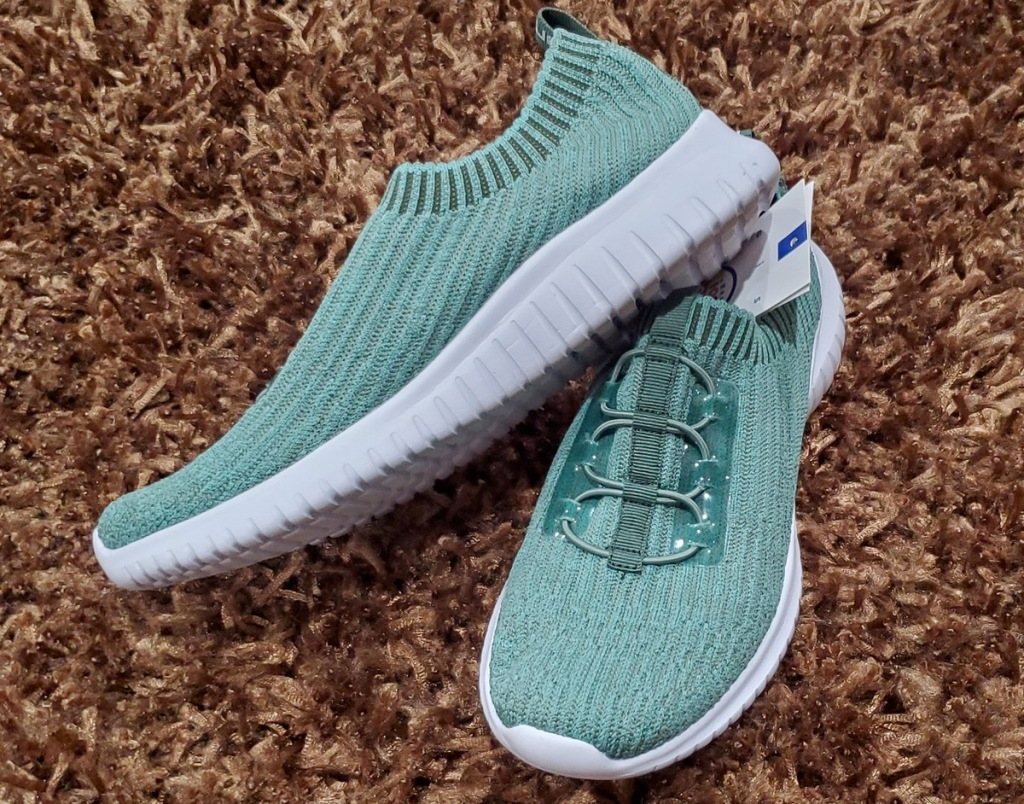 pair of light green women's knit sneakers with elastic laces on a brown carpet