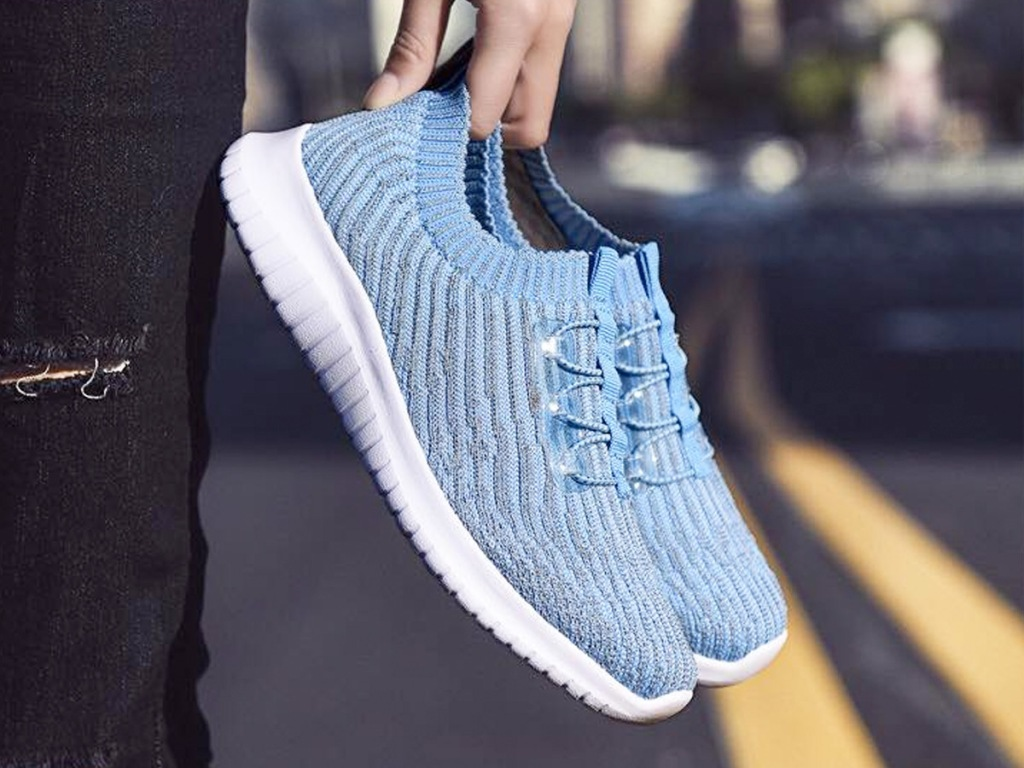 person holding a pair of blue knit slip-on sneakers with white rubber soles