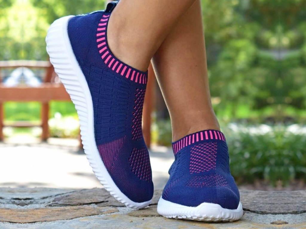 person wearing a pair of navy blue and pink slip-on walking shoes with white rubber soles