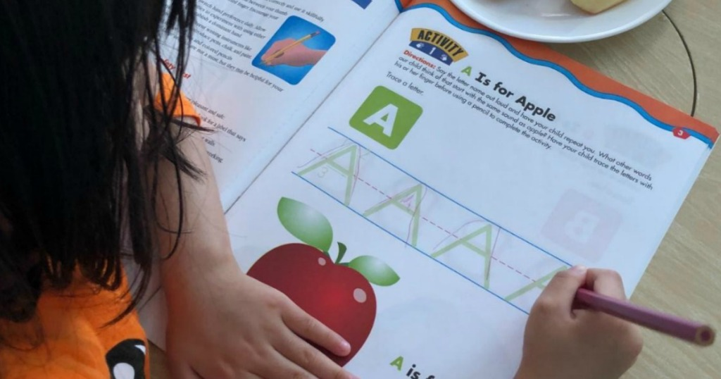 girl tracing letters in a workbook