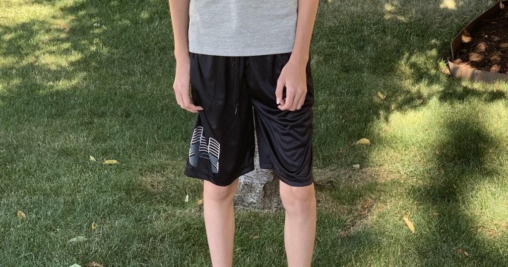 boy standing on grass in black sport shorts