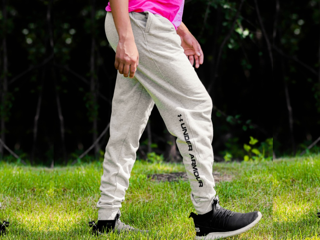 man wearing Under Armour Men's UA Rival Graphic Joggers in grey with a pink shirt on