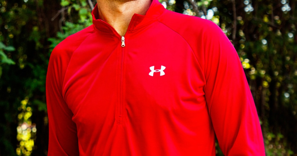 man wearing a bright red half-zip pullover with white under armour logo on chest