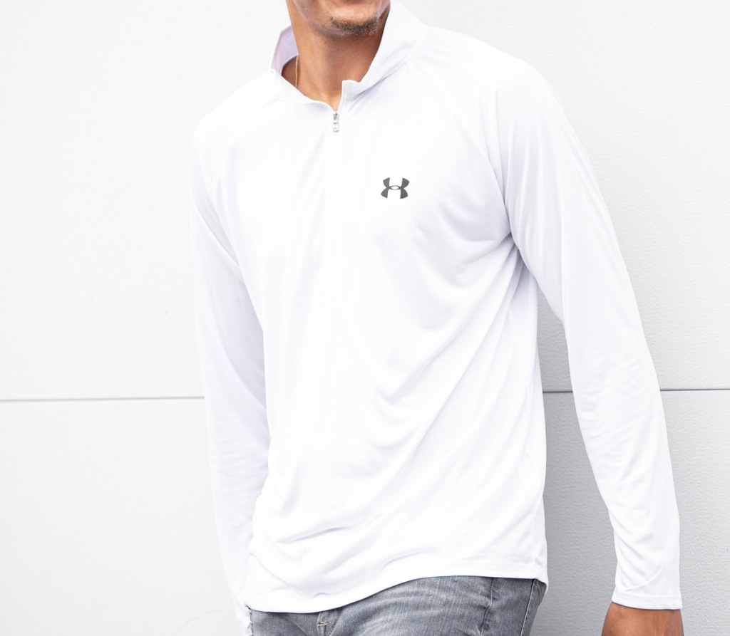 man leaning against white wall wearing a white under armour half-zip pullover