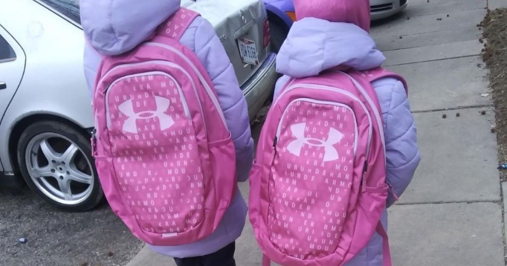 two girls wearingmatching under armour backpacks
