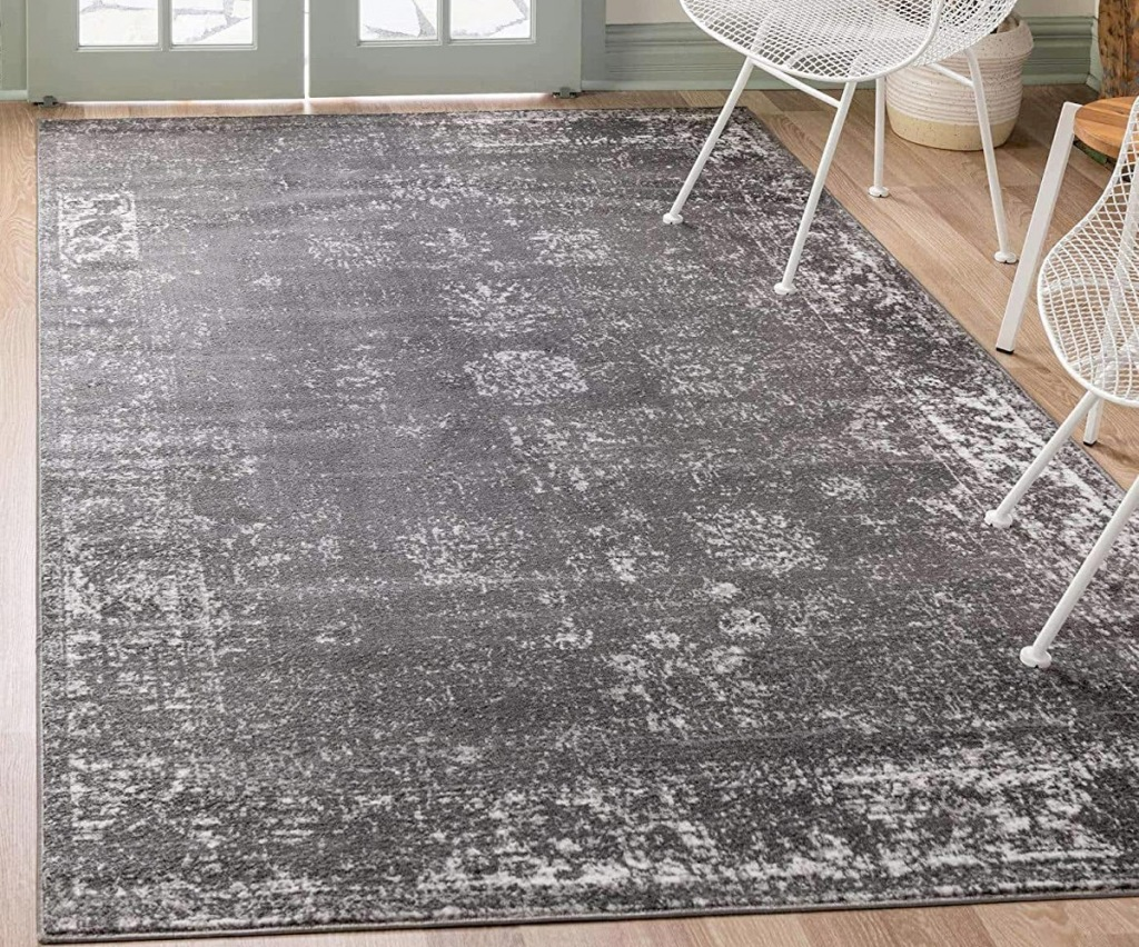 dark grey area rug on hardwood floor near white chairs