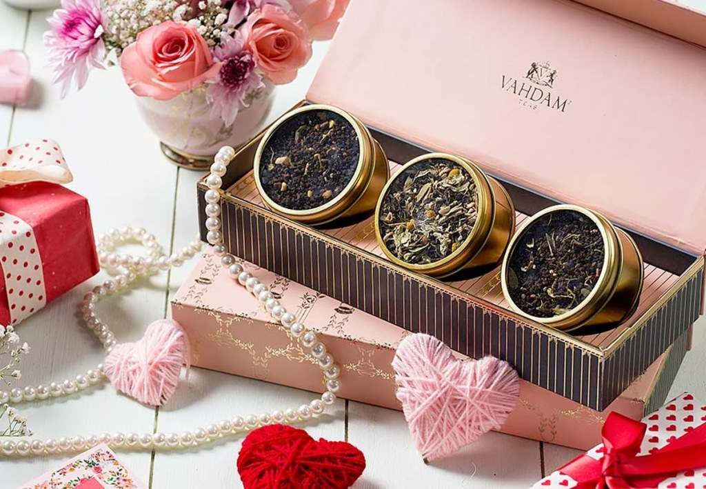 three round containers of loose leaf tea in pink box with hearts and flowers on table around it