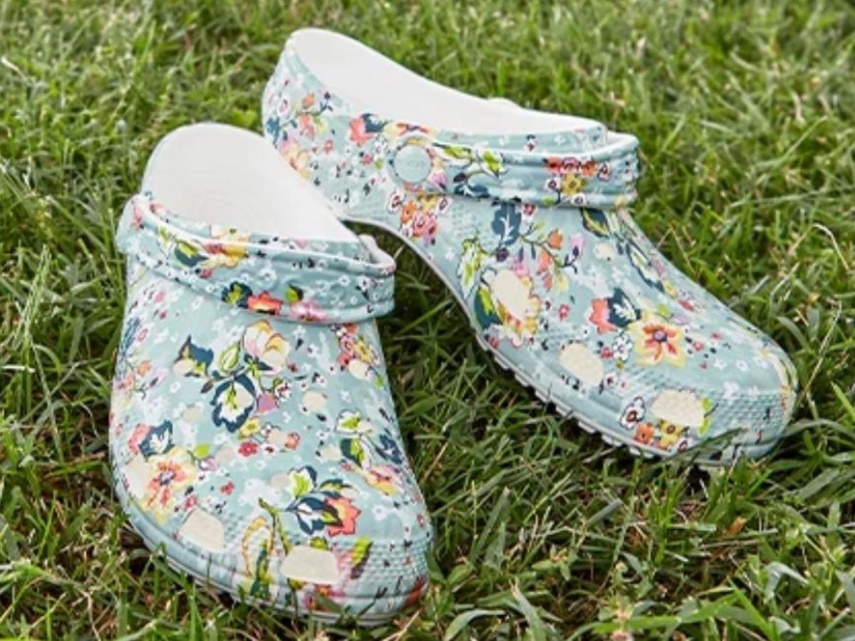 pair of floral print clogs resting on grass