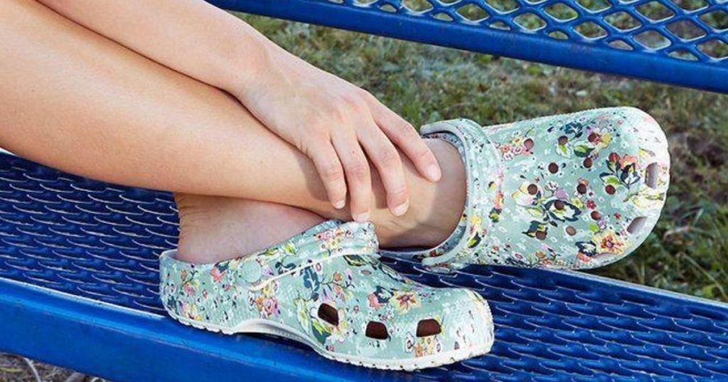 Woman wearing crocs sitting on bench